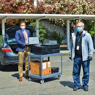 Picture of Winlock School Superintendent Garry Cameron (left) helps load laptops into his car with Northwest/Arctic Region Regional Administrator Roy Atwood (right) while observing social distancing.