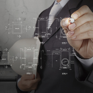 A stock image of a man in suit cropped at the neck holding a hardhat and using a stylus to point at blueprint images on the screen