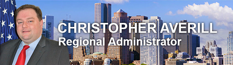 Christopher Averill, Regional Administrator, with portrait and daytime Boston skyline